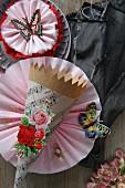 Dekoidee für Party: Kegelförmige Papiertüte mit Blume aus rosa Krepp-Papier und Papierschmetterling