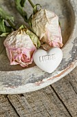 Two dried roses and heart-shaped soap with love message on vintage clay dish
