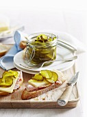 Bread and butter pickles (pickled gherkins with mustard and vinegar) in preserving jar and on slice of bread
