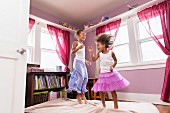 Two little girls wearing skirts bouncing on a mattress