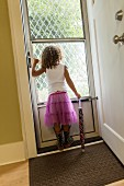 Girl wearing violet tulle skirt looking out through glazed door
