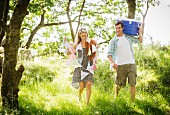 Young couple in forest with bunting and cool box