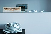 Stack of polygonal plates below paper boats and Nordic painting arranged on half-height wall