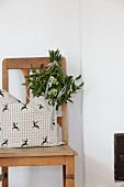 Old wooden chair with cushion and posy of mistletoe and Star-of-Bethlehem flowers hanging from backrest