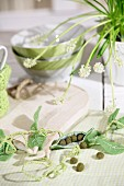 Spring arrangement with felt pea pods on table set with wooden boards and cereal bowls