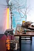 Essplatz mit Accessoires im modernen Jägerstil - dürres Baumwerk und gelbe Leuchtröhre vor Landschaftsposter; Holzbündel und rustikales Sackleinen