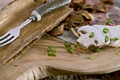 Sliced mushrooms and spring onions on wooden board; rustic fork with horn handle in bark dish