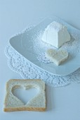 Heart-shaped slice of bread on doily on white place setting