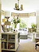 White sideboard with shelf compartments and bay window with round table, sofa & checked Roman blinds