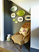 Traditional easy chair in niche below stairs painted grey with collection of plates on wall