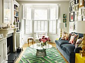 60s table on rug with geometric pattern and floral scatter cushions on sofa; bay window with interior shutters in background