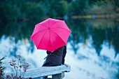 Woman with pink umbrella sitting by lake