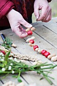 Threading crab apples and peanuts onto string