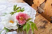 Zwei Pfingstrosenblüten in Körbchen als Deko auf rustikalem Holztisch