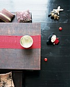 Low, Oriental table decorated with red runner and small cushions on benches; Oriental fabric doll on black-varnished wooden floor