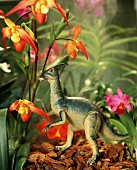Toy dinosaur next to flowering orchid
