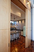 View through open, wooden sliding elements of kitchen counter, pendant lamps, bar stools and fridge