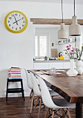 Dining area in mixture of styles - classic chairs at rustic walnut table and yellow-framed station clock next to hatch