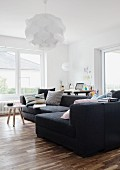 Charcoal sofa on walnut floor and sculptural pendant lamp in minimalist living room