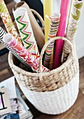 Rolls of colourful, patterned wrapping paper in white basket