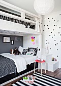 White wooden bunk beds with black and white bed linen and striped rug in children's bedroom