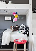 Bunk beds with soft toys and black and white bed linen against mid-grey wall and stool with pink seat in foreground