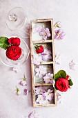 Lila Blüten und rote Rosen als Tischdeko