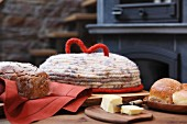 Hand-crocheted felt bread cover, fresh bread and butter on wooden table