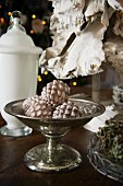 Fir cone baubles in silver footed dish and white glass vessel with lid on table