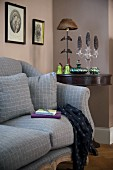 Sofa with grey upholstery and matching scatter cushions next to festively decorated console table
