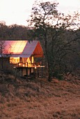 Beleuchtetes Ferienhaus in Abendstimmung in afrikanischer Landschaft