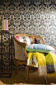 Cushions & blankets on antique armchair in front of wall with patterned wallpaper