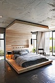 Comfortable double bed on modern, floor-to-ceiling bed platform with canopy in light-flooded interior with concrete ceiling and open terrace doors