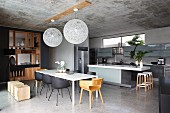 Open-plan, designer kitchen-dining area with elegant, purist, fitted wooden partition shelves; two spherical pendant lamps hanging from concrete ceiling