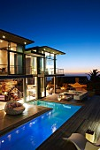 Luxushaus mit L-förmigem Pool und Terrasse beleuchtet in märchenhafter Abendstimmung mit Meerblick