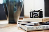 Antique camera on stack of books in front of vase on table