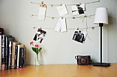 Vase of flowers and row of books next to antique camera and table lamp below black and white photos on wall