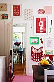 Framed colourful fabric samples and pictures on kitchen wall, fruit bowl on antique wooden table, open door with view of dining area