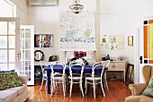 Rustic interior with white-painted Thonet chairs, deep blue dining table, pictures on wall and French windows to one side