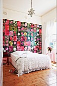 Double bed with white lace bedspread against wall covered in pictures of flowers in rustic interior