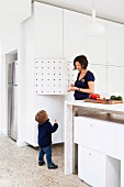 Mother and child in open-plan kitchen; stone counter with white modules below and floor-to-ceiling white fitted cupboards