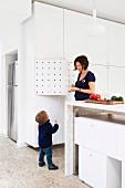 Mutter mit Kind in offener Küche, Küchentheke aus Stein und eingeschobenen, weissen Schrankmodulen; seitlich raumhoher, weisser Einbauschrank