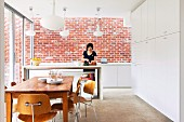 Dining area in front of kitchen counter, woman preparing food, exposed brick wall, tall white fitted cupboards and classic chairs in modern, open-plan kitchen
