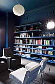 Dark blue bookshelves on dark wall with porthole window contrasting with white easy chairs and white spherical ceiling light