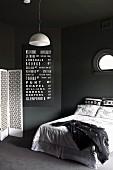 Schwarzer Schlafraum mit weissen Farbakzenten; französisches Bett unter Bullauge, weiße Pendellleuchte und weißer Paravent, schwarze Wandtafel mit weisser Schrift