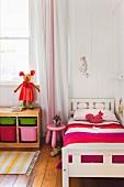Bunte Möbel im Kinderzimmer mit Holzboden und Bretterwand