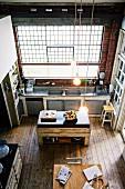 Gräumige Vintage-Küche im Loft eines alten Industriegebäudes mit Dielenboden und Ziegelwand