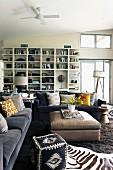 Loungebereich mit afrikanischen Kleinmöbeln, Zebrafell, graue Sofagarnitur mit Kissen um gepolsterten Couchtisch im Hintergrund weißes Wandregal
