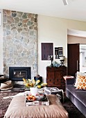 Vase of flowers on tray on ottoman, African pouffe on animal-skin rug and fireplace in stone chimney breast
