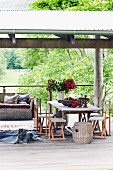 Rustic wooden table and chairs, dog lying on animal-skin rug and wicker sofa with cushions on roofed wooden terrace in summery landscape